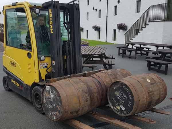 Mit Gabelstaplern werden auf dem Gelände der Ardbeg-Destillerie die Whiskyfässer transportiert.