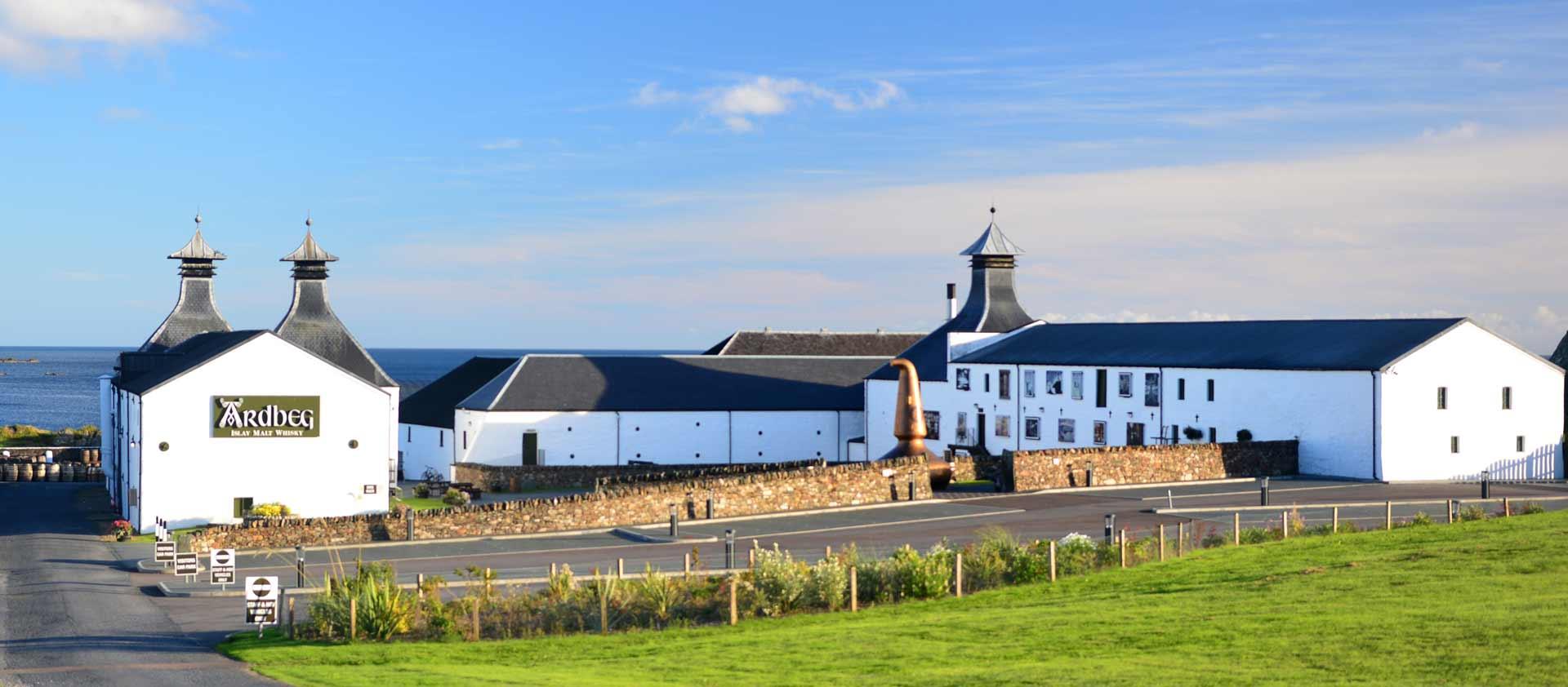 Ardbeg. Blick auf die Destillerie an einem Smmerabend mit strahlend blauem Himmel.